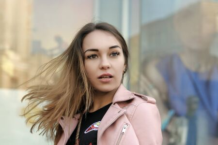 Portrait of an attractive girl on the background of a glass shop window of womens cosmetics. The girl is dressed in a pink jacket and the wind is waving her hair. Stock Photo