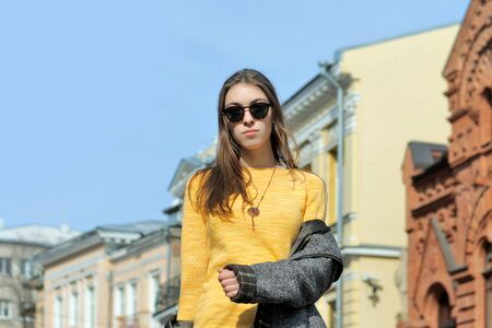 Beautiful girl is walking along the sidewalk. The weather is hot and she took off her coat on the go. She is dressed in a yellow sweater and sunglasses. In the background you can see the sky and the buildings of classical architecture