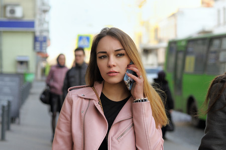 frowns: Beautiful girl talking on the phone while walking on the sidewalk in the city. Shes in a bad mood and she frowns. It is cold and she is dressed in a leather pink jacket. Stock Photo
