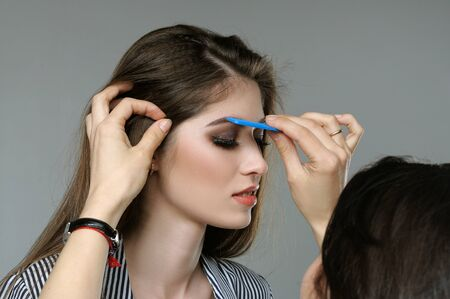 threading hair: Master corrects the eyebrows of the model before shooting. Studio portrait against a gray background. Stock Photo