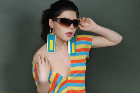 Portrait of a brunette in sunglasses and striped blouse. She bare her shoulder and in the girl's ears wear earrings in the form of tags of clothes.