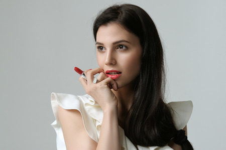 Portrait of three-quarters of a woman who holds a lipstick between the fingers near the face. She has daytime makeup, perfect skin, neat red nails and long dark hair