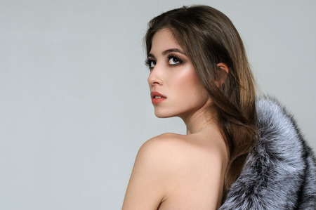 Beauty portrait of a girl with bare shoulders and fur coat against a gray background Stock Photo