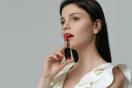 Portrait of a cute girl who holds a lipstick near her lips like a revolver. She has daytime makeup, perfect skin, neat red nails and long dark hair