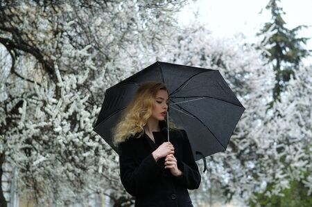 Blonde stands under the umbrella in the rain against the background of flowering apricot trees