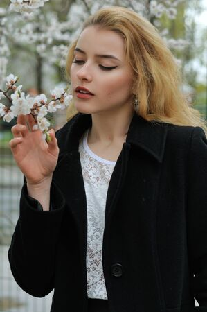 Girl enjoys the smell of flowering apricots while walking along the avenue