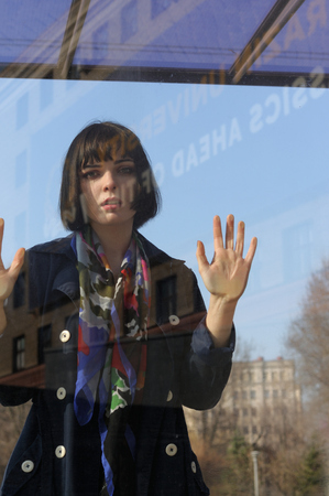 Girl leaned her hands on the window glass. She has brown hair and a bob hairstyle, she is wearing a blue raincoat and a scarf around her neck.
