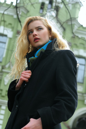 Fashion portrait of an elegant girl who poses against a background of urban architecture. She has long blond hair and she is dressed in a black coat and blue scarf