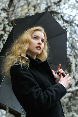 Girl with blond hair stands under an umbrella in the rain against the background of flowering apricot trees