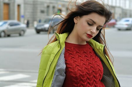 Beautiful girl with long brown hair walks around the city. She is dressed in a salad jacket and a red sweater Stock Photo