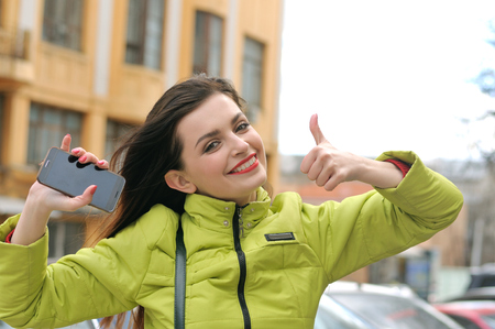 Portrait of a stylish girl who walks around the city and the wind blows her long brown hair. She is dressed in a green jacket and has a good mood.