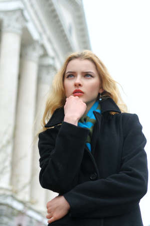 Fashion portrait of a beautiful blonde with long hair against urban architecture of classical style Stock Photo