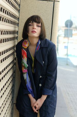 Beautiful girl standing near the closed roller shutters store. She has brown hair and a bob hairstyle, she is wearing a blue raincoat and a scarf around her neck.