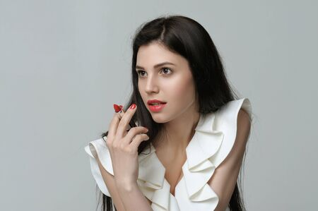 Girl is holding lipstick in her hand like a cigar. She has daytime makeup, perfect skin, neat red nails and long dark hair Stock Photo