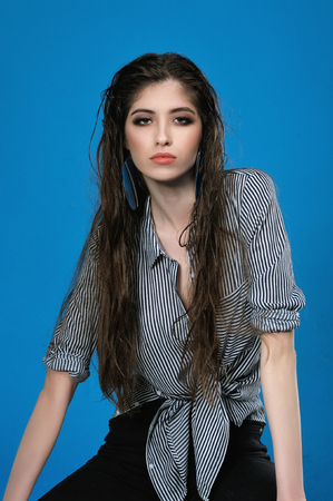 Studio portrait of a beautiful girl with long wet hair who is dressed in a striped shirt tied on her stomach