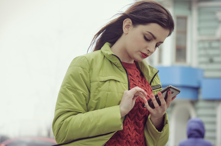 Girl is talking on the phone while walking around the city. She has long brown hair and is dressed in a light green jacket