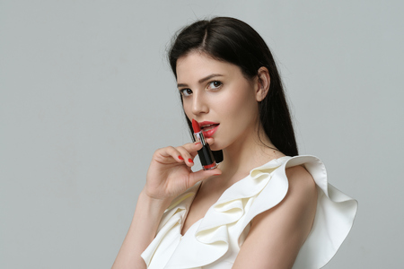 Mysterious girl who keeps lipstick near her lips like a revolver. She has daytime makeup, perfect skin, neat red nails and long dark hair Stock Photo