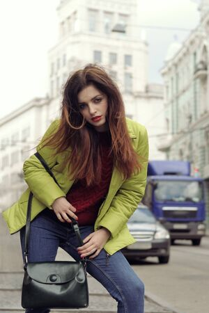 Girl with long brown hair walks around the city. She is wearing a light green jacket and blue jeans Stock Photo