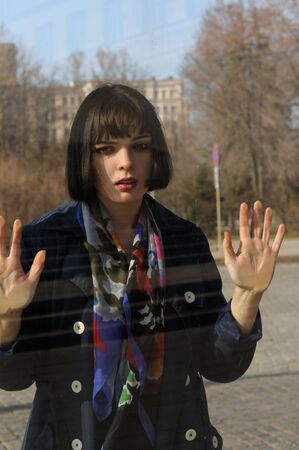 Woman leaned her hands on the window glass. She has brown hair and a bob hairstyle, she is wearing a blue raincoat and a scarf around her neck. Stock Photo
