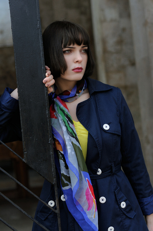 Portrait of a stylish girl near a metal railing. She has brown hair and a bob hairstyle, she is wearing a blue raincoat and a scarf around her neck. Stock Photo