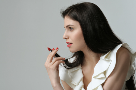 Portrait in profile of a pretty girl who is holding a lipstick like a cigar. She has daytime makeup, perfect skin, neat red nails and long dark hair