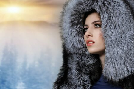 Portrait of a beautiful girl in a gray fur hat on a background of a winter landscape and a setting sun