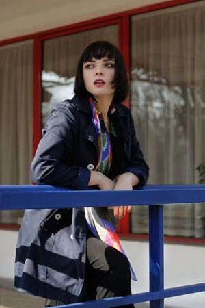 Fashionable girl is waiting for transportation. She has brown hair and a bob hairstyle, she is wearing a blue raincoat and a scarf around her neck.