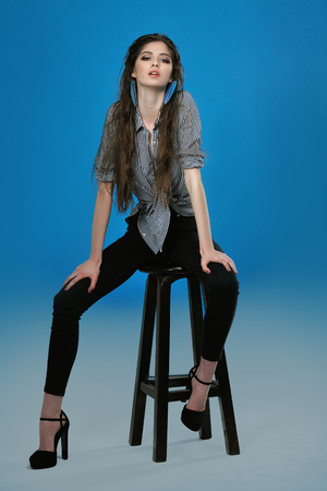 Full-length portrait of a model who poses for tests against a blue background in the studio