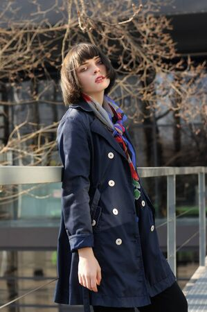 Girl leaned her back on the railing in the park. She has brown hair and a bob hairstyle, she is wearing a blue raincoat and a scarf around her neck. Stock Photo