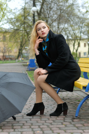 Beautiful girl sits on the bench in the park and at her feet lies an open umbrella