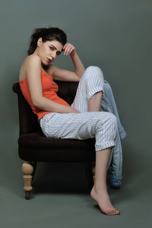 Portrait of a brunette in full growth in the studio, who sits in an armchair against a green background. She is dressed in an orange T-shirt, white trousers in thin stripes and a jeans jacket hanging on the chair.