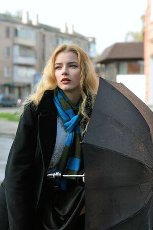 Portrait of a girl who stands under an umbrella in the rain against a city street background