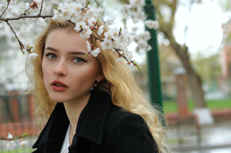 Portrait of a girl with blond hair who walks under blooming apricot trees