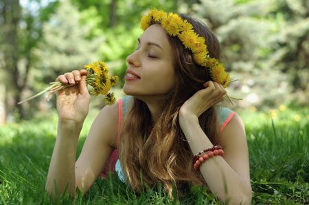 he girl lies on the grass with a wreath of wild flowers on her head in an outdoor park
