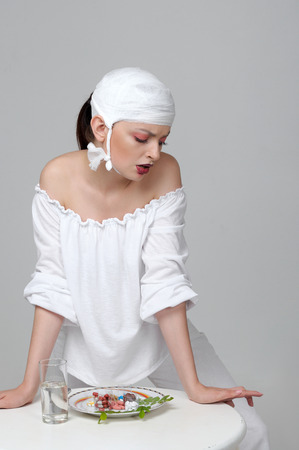 Portrait of a girl who has food from medicines instead of food. She is dressed in white robes and a bandage is tied on her head