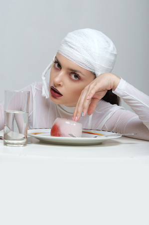 Fashion portrait of a girl with a bandage on her head who eats frozen strawberries in jelly Stock Photo