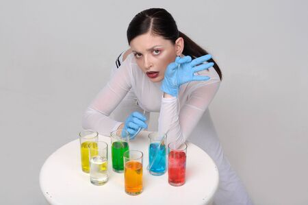 Fashion portrait of a girl who drinks chemical liquids instead of natural juices