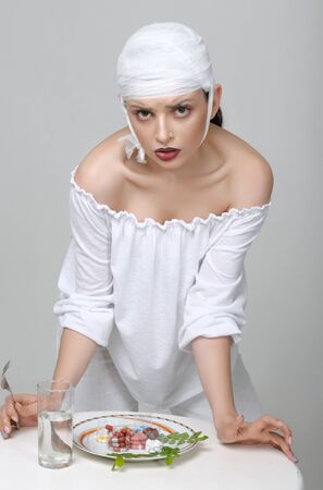 Fashion portrait of a girl with a bandage on her head who stands at the table and has a lunch of medicines