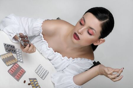 Fashion portrait of a girl who sits at a table and sorts through the packs of medicines