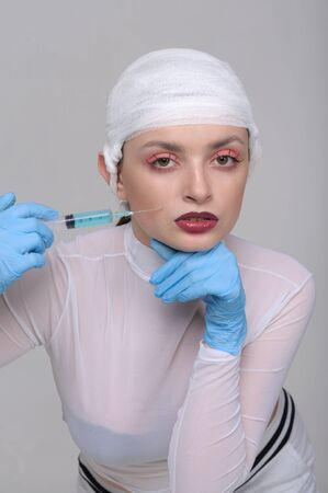 Fashion portrait of a girl with a bandage on her head who pricks drugs for skin beauty