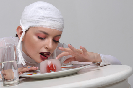 Fashion portrait of a sick girl with a bandage on her head who eats artificial food