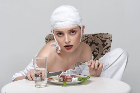 Fashion portrait of a girl with a bandage on her head who sits at the table and has a lunch of medicines