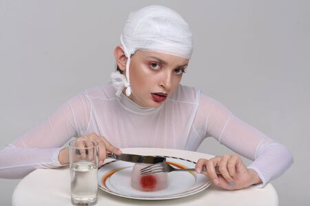 Fashion portrait of a sick girl with a bandage on her head who eats artificial food Stock Photo - 81051521