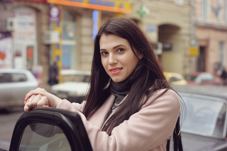 Girl gets into the car. She is dressed in a coat and has long brown hair Stock Photo - 81268921