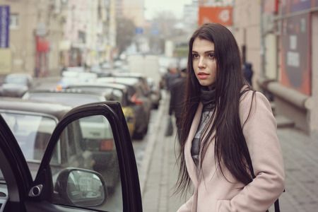 Girl gets into the car. She is dressed in a coat and has long brown hair Stock Photo - 81291082
