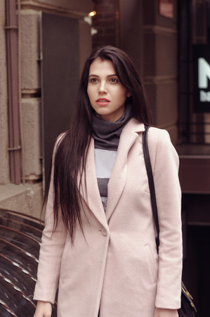 Model shows autumn clothes. She is dressed in a coat and has long brown hair Stock Photo