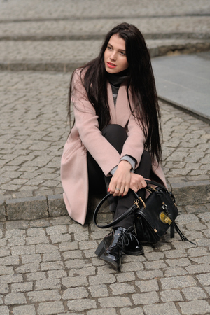 Model shows autumn clothes sitting on the sidewalk. She is dressed in a coat and has long brown hair