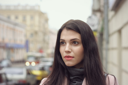 Girl goes through the city in the early spring. She is dressed in a coat and has long brown hair Stock Photo - 81140183