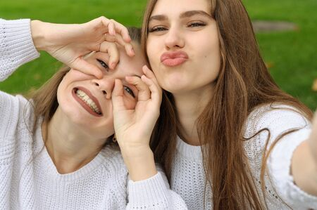 Two girlfriends are fooled by showing grimaces, while they make a selfie photo. They both have long brown hair that is long to the waist and they are dressed in identical white sweaters. Stock Photo - 91267859