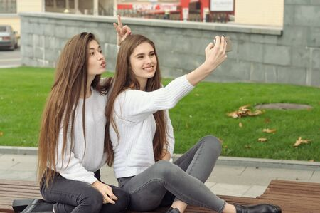 Girl shows the horns to the girlfriend while they make a selfie photo. They both have long brown hair that is long to the waist and they are dressed in identical white sweaters.